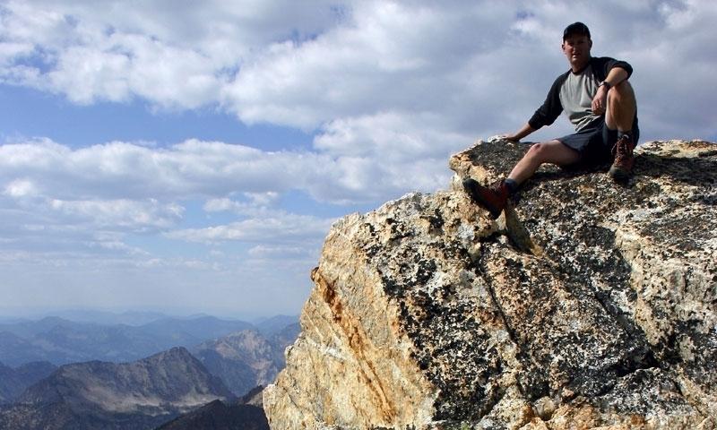 Climber sitting atop Thompson Peak
